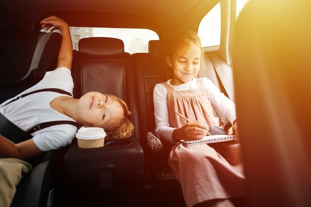 Rusteloze broers en zussen rijden op een achterbank in een auto. uitzicht vanaf binnen salon. jongen verveelt zich, hij heeft geen dingen meer te doen. meisje is aan het tekenen.