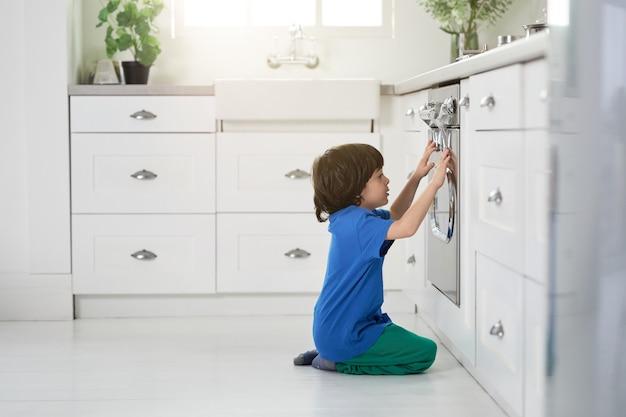 Rusteloze kleine spaanse jongen kijkt naar het bakken van cake in de oven, gehurkt in de keuken. kinderen, kookconcept. zijaanzicht