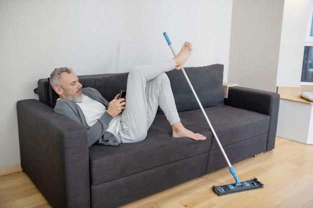 Rusten. een man die wat rust heeft na het schoonmaken van het huis