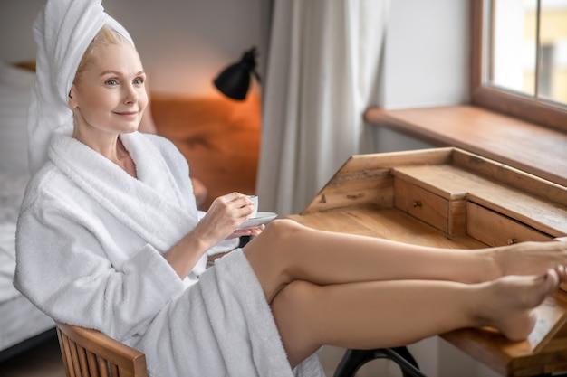 Rusten. een vrouw in een wit gewaad zit bij het raam en drinkt thee