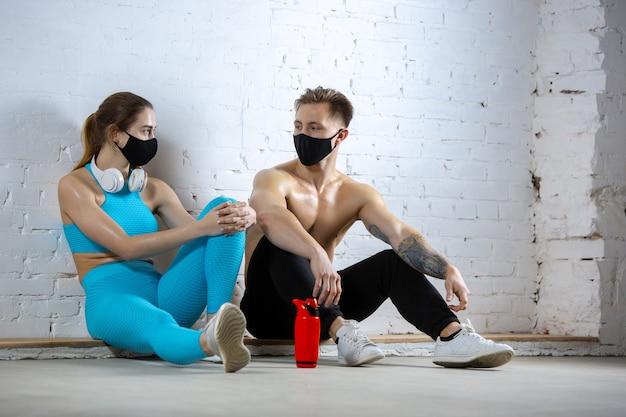 Rusten. professionele atleten die op bakstenen muur trainen die gezichtsmaskers dragen. sport tijdens quarantaine van coronavirus wereldwijde pandemie. jong koppel oefenen in sportschool veilig met behulp van apparatuur.