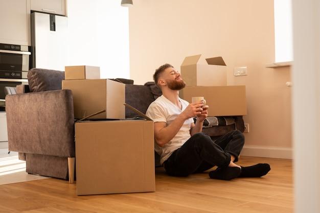Rustende jonge man zittend op de vloer en het drinken van thee of koffie. blij europese man met gesloten ogen in de buurt van sofa. kartonnen dozen met dingen. concept van verhuizen in nieuwe flat. interieur van studio appartement