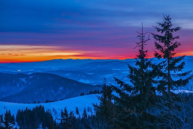 Rustgevend landschap in de bergvallei met sparrenbos en sneeuwbanken tegen de achtergrond van geen zonsondergang en blauwe lucht met wolken. concept van openluchtrecreatie. advertentie ruimte