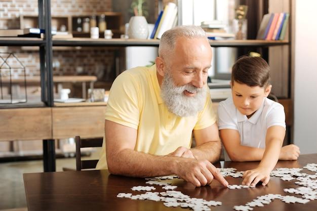 Rustgevend tijdverdrijf. gelukkig senior man zit aan de tafel naast zijn kleinzoon en probeert een grote puzzel met hem te maken Premium Foto