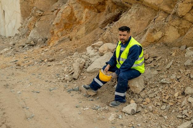 Rustgevende bouwer in uniform met pauze op de bouwplaats