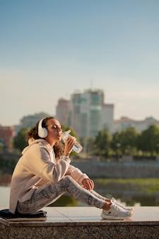 Rustgevende dorstige vrouw in sportkleding drinkwater uit de fles zittend tegen rivieroever na buitentraining en genieten van muziek