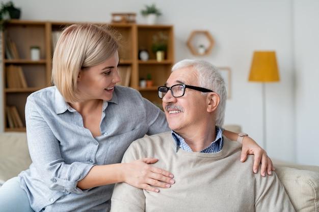 Rustgevende senior man en zijn jonge dochter ontspannen op de bank, glimlachen en kijken elkaar terwijl praten thuis