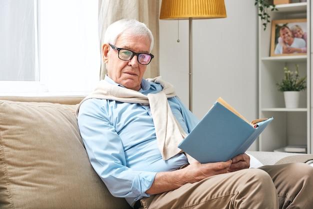 Rustgevende senior man in bril, shirt en broek op zoek naar jou terwijl je open boek vasthoudt en ontspant op de bank