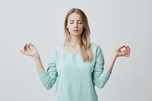 Rustgevende, vreedzame blonde vrouw voelt zich ontspannen, staat in lotushouding, probeert zich te concentreren of gefocust te zijn, sluit ogen, geniet van stilte, probeert evenwicht te vinden. rustige sfeer en meditatie