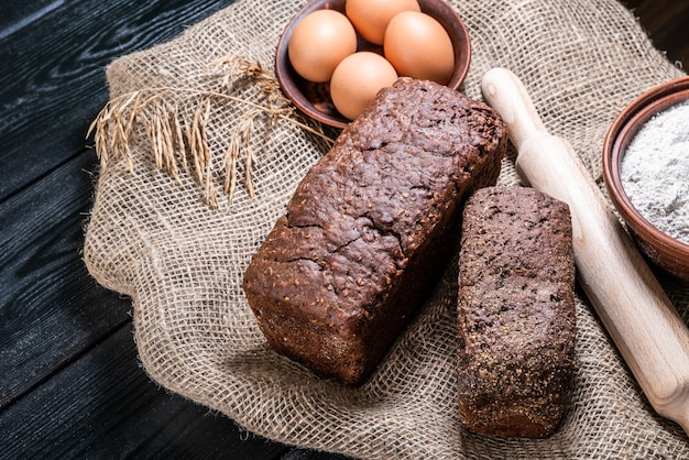 Rustiek brood en tarwe op donkere houten tafel. donkere humeurige achtergrond met vrije tekstruimte.
