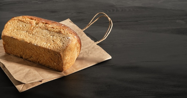 Rustiek brood op een papieren zak op zwarte houten tafel is voorbereid voor levering aan de koper. idee voor een klein bedrijf, bakken en bezorgen van gezond natuurlijk zuurdesembrood op bestelling. bovenaanzicht met kopie ruimte