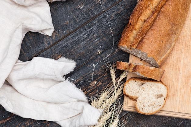 Rustiek brood op houten tafel met tarwe en doek