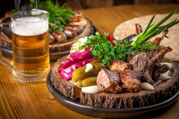 Rustiek eten en veel gebakken vlees op een tafel, met een glas bier