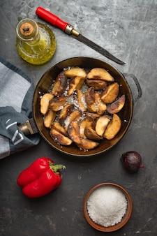 Rustiek eten. gebakken aardappelen in een pan op een donkere betonnen tafel. rustieke stijl.