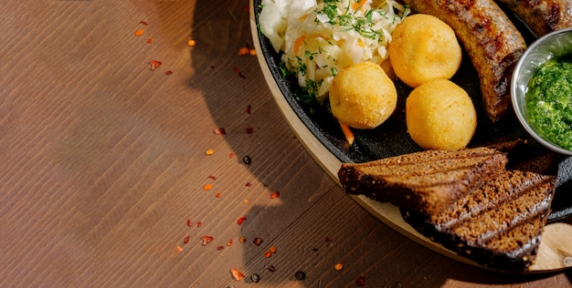 Rustiek eten met geroosterde worst gebakken aardappelen op een bord met bestek, bovenaanzicht. duits voedselconcept