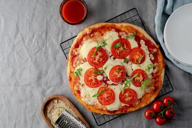 Rustiek italiaans huisgemaakt pizzadeeg margherita overgoten met pizzasaus van tomaten uit blik, mozzarella kaas en rucola op donker linnen tafelkleed