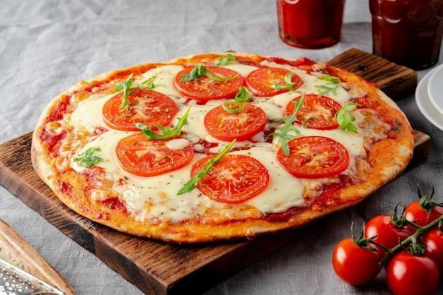 Rustiek italiaans zelfgemaakt pizzadeeg margherita gegarneerd met pizzasaus van tomaten uit blik, mozzarella kaas en rucola op donker linnen textiel tafelkleed, zijaanzicht