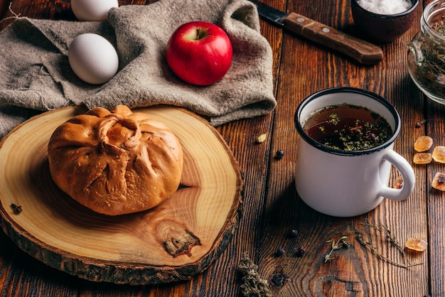 Rustiek ontbijt met traditionele tatar gebak elesh, kruidenthee in metalen mok