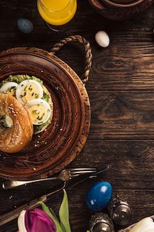 Rustiek paasontbijt plat lag met eieren, bagels, tulpen, croissants, ei, havermout met bessen, gekleurde kwarteleitjes en decoraties voor de lentevakantie. bovenaanzicht, kopieer ruimte