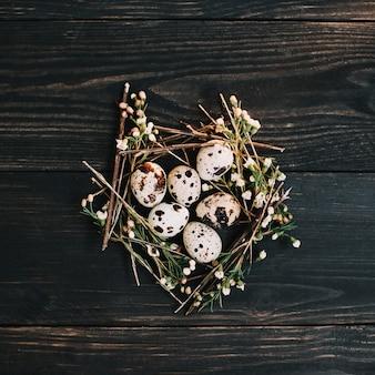 Rustiek pasen-stilleven met kwarteleitjes en wilgentakken op donkere houten achtergrond