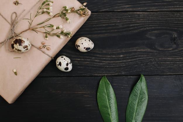 Rustiek pasen-stilleven met kwarteleitjes, wilgentakken, konijnenoren en decoraties op donkere achtergrond