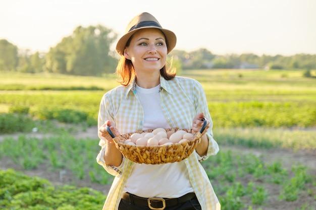 Rustiek portret van rijpe vrouw met mand van eieren bij weide