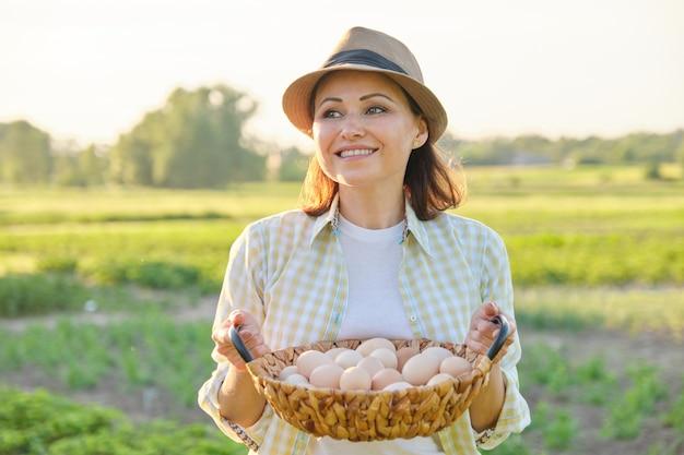 Rustiek portret van volwassen vrouw met mand met eieren op weide