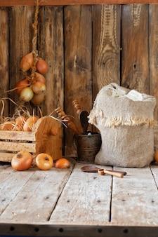Rustiek stilleven, bloem, uien, eieren en kruiden op een houten tafel.