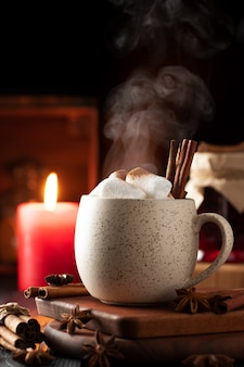Rustiek stilleven met warme drank, kaneel en marshmallows.