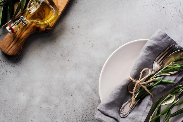 Rustiek vintage bestek. plaat met grijze linnenservet, vork en lepel, olijfboomtak over rustieke concrete grijze oud. instelling tafeldecoratie herfstvakantie.
