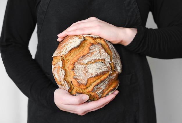 Rustiek volkoren zuurdesembrood, handen met vers brood