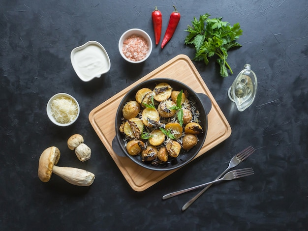 Rustieke aardappelen met champignons op een zwarte tafel. bovenaanzicht.