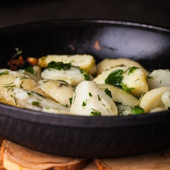 Rustieke gepofte aardappel met kruiden in koekenpan