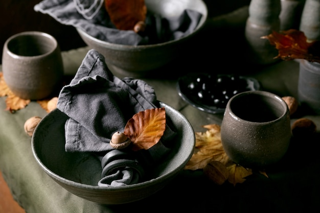 Rustieke herfst halloween- of thanksgiving-tafel met leeg ambachtelijk keramisch servies, grijze ruwe kommen en kopjes op linnen tafelkleed met herfstgele bladeren en eikels. donkere achtergrond