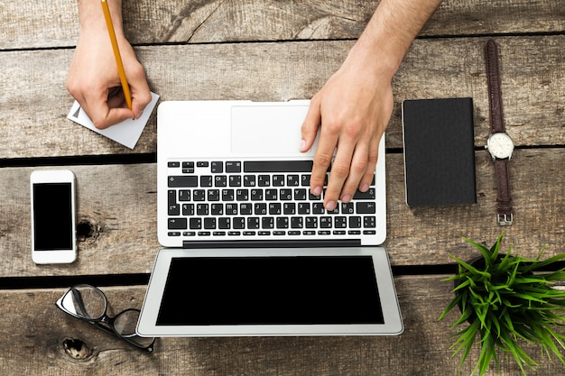 Rustieke hipster houten bureaublad bovenaanzicht, mannelijke handen met behulp van laptop