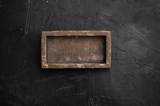 Rustieke houten kist of containerset met kopieerruimte voor tekst of voedsel, bovenaanzicht plat gelegd, op zwarte donkere stenen tafelachtergrond