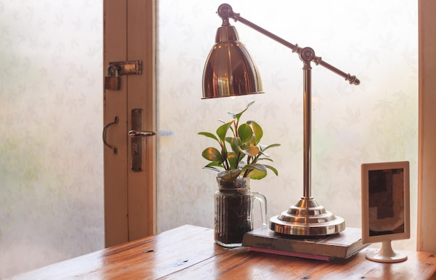Rustieke houten leestafel met warm daglicht verlicht door glazen deur.