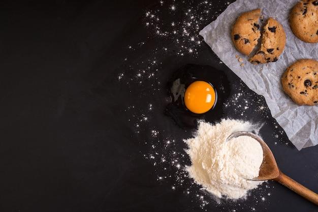 Rustieke houten lepel met een bloem, een rauw ei, een bakpapier en koekjes op een zwart bord