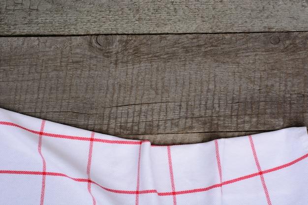 Rustieke houten planken met een rood geruit servet met kopie ruimte voor uw menu of recept.