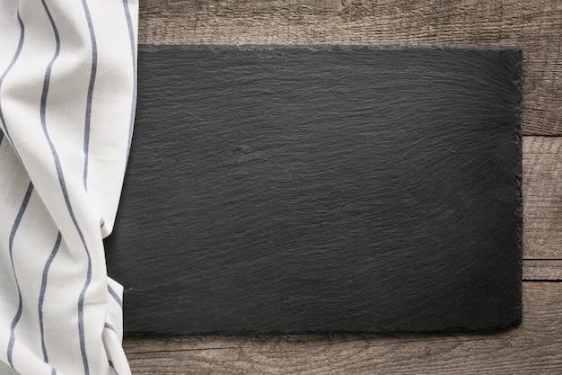 Rustieke houten planken, wit servet gestreept met en zwarte leisteen schotel met kopie ruimte voor uw menu of recept.
