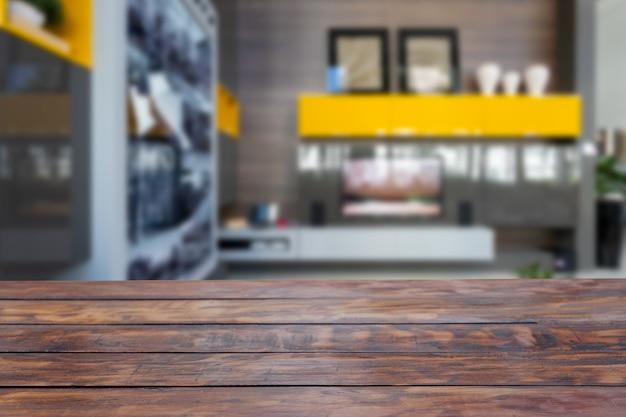 Rustieke houten tafel op de voorgrond met een woonkamer met gele accenten op de onscherpe achtergrond.