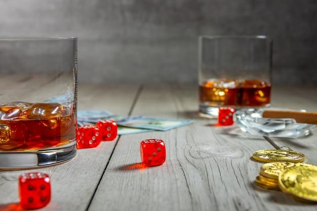 Rustieke houten tafel. twee glazen whisky met ijsblokjes en een sigaar in een asbak. dollarbiljetten en dobbelstenen. een paar bitcoin-munten