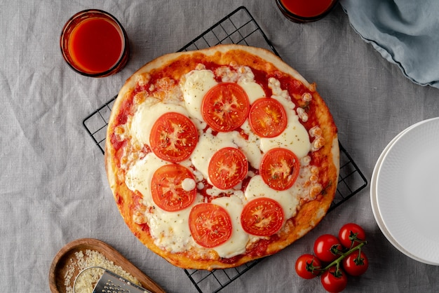 Rustieke italiaanse zelfgemaakte pizzadeeg margherita gegarneerd met pizzasaus op donkere tafel