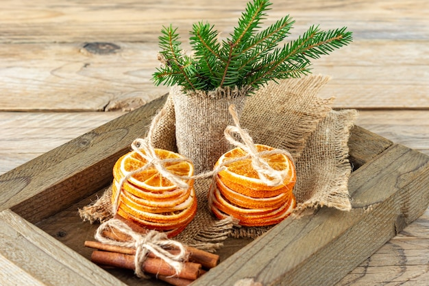 Rustieke kerstcompositie met gedroogde sinaasappelen, kaneelstokjes en dennenboomtakken in een houten kist.