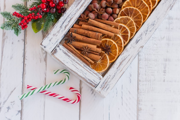 Rustieke kerstcompositie met gedroogde sinaasappels, kaneelstokjes en dennenboomtakken in een houten kist. bovenaanzicht met kopie ruimte.