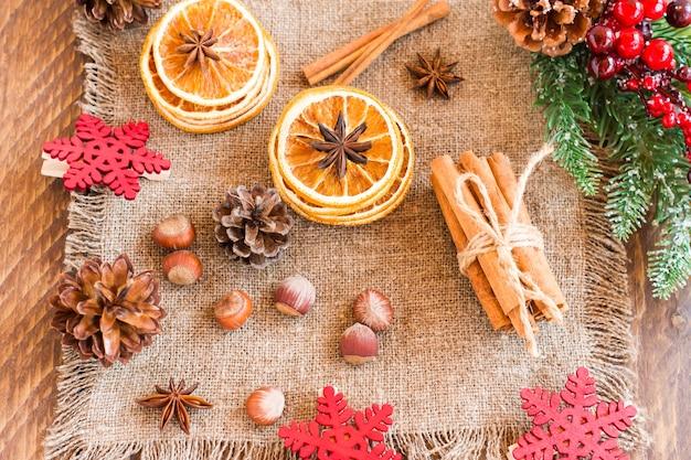 Rustieke kerstcompositie - vuren tak met bessen en kegels, gedroogde sinaasappelschijfjes, noten, onis op jute. bovenaanzicht.