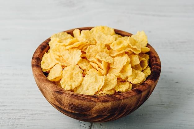 Rustieke kom cornflakes over houten oppervlak