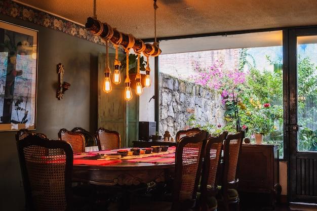 Rustieke kroonluchter gemaakt van bollen en touwen boven een eettafel in een vintage keuken