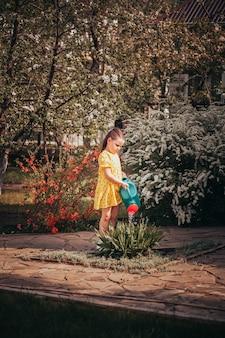 Rustieke levensstijl een meisje in een gele jurk geeft bloemen water uit een tuingieter en helpt haar pa...