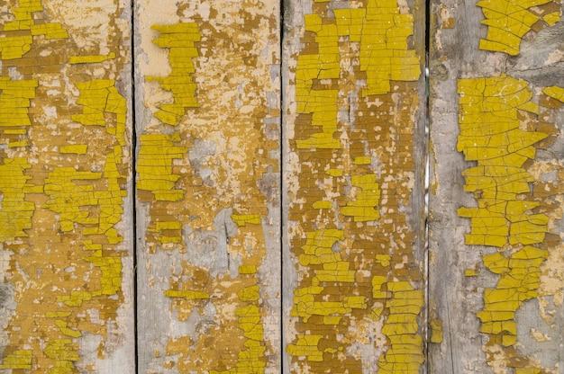 Rustieke omheiningsachtergrond geschilderd met gele verf, die is gewist
